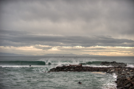 Marina Park surfers withstanding incoming rainy storm at dawn patrol.