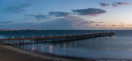 Panoramic sweep of Ventura Pier as dusk settles over Pacific Ocean.