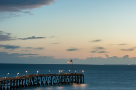 American Flag waving in sea breeze at end of Ventura Pier at dusk. Stock Photo