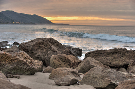 breaking waves: Barnacle covered rocks immovable to the breaking waves of California.