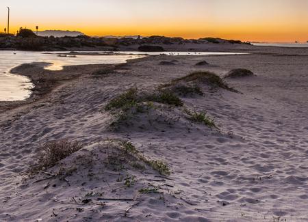 berm: Natural sand berm creates levee for estuary water shoreline. Stock Photo