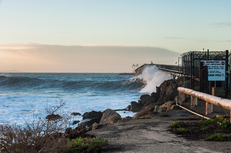 Landscape view of large set wave spraying Richfield Pier with Rincon Island in background.