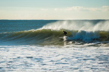 agachado: Surfer ducking under the wave lip as off shore winds blow. Foto de archivo