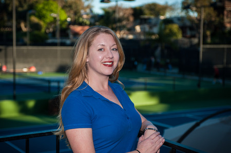 fair skinned: Fair skinned red head woman smiling while wearing blue polo shirt. Stock Photo