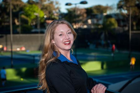 fair skinned: Fair skinned red head woman smiling while wearing black athletic jacket.