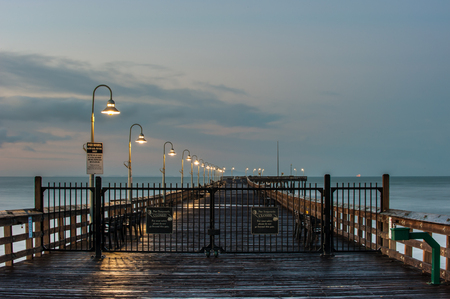 Lamps glowing along Ventura Pier as the sun begins to rise. Stock Photo