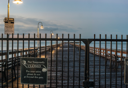 Locked gates across Ventura Pier as lamps glow in background. Stock Photo
