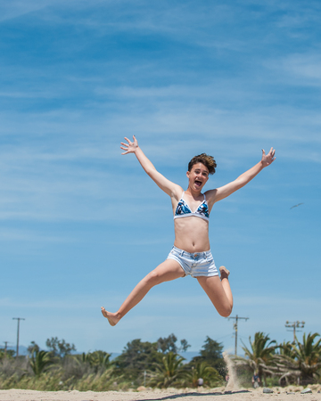 Teenage girl jumping for joy with the blue California Spring sky in background.