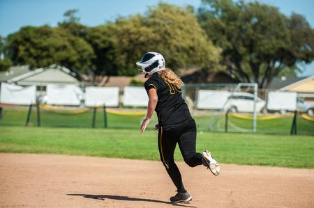 Black uniform softball player running around to second base. Stock Photo