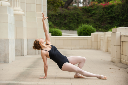Beautiful and young ballerina supported on one arm while reaching to sky.