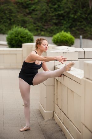 Beautiful and young ballerina reaching for her toes with leg up on wall.