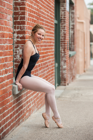 sil: Youthful ballerina seated in red brick window sill with happy expression. Stock Photo