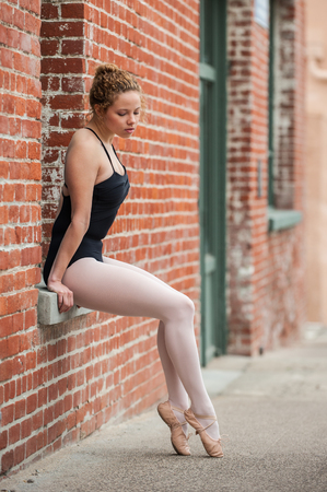 Youthful ballerina seated in red brick window sill while looking at slipper. Zdjęcie Seryjne