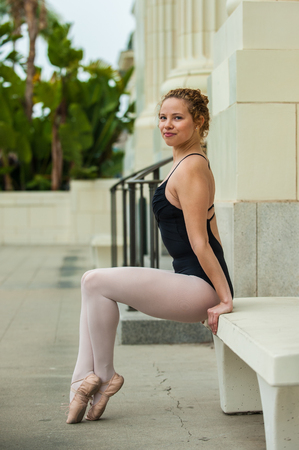 Beautiful and young ballerina seated with toes pointed. Stock Photo