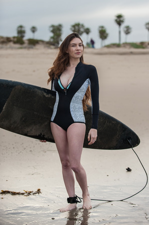 Sexy California surfer girl holding board with wetsuit top unzipped looking to right. Stock Photo