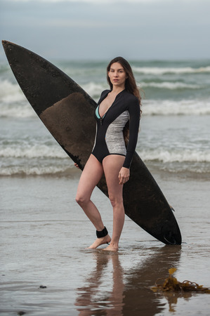 Sexy California surfer girl holding black surf board standing on reflection in shallow water. Stock Photo