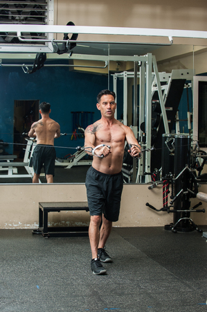 Middle age muscular man performing cable chest press exercise with back reflected in mirror and serious expression.