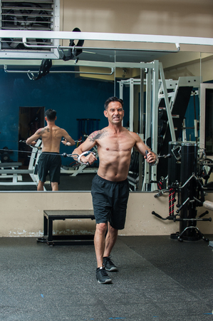 Middle age muscular man performing cable chest press exercise with back reflected in mirror and intense expression. Stock fotó