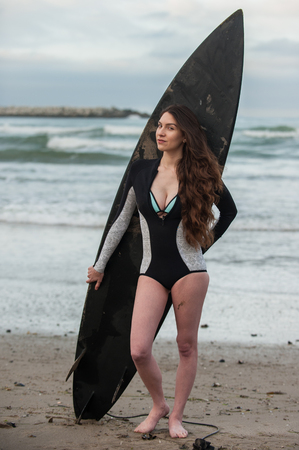 Sexy California surfer girl standing with back to board and waves looking left in full view. Stock Photo