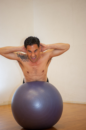 Middle age Japanese man performing back extension on stability ball with intense expression and strong core.