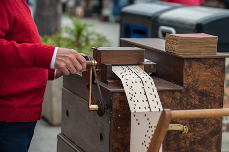 Large hand cranked music box on by street vendor with punch card feed.