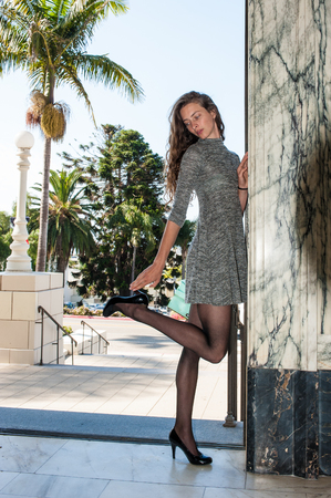 Pretty brunette in black pantyhose, short dress, and pumps leaning on wall while looking down kicking up heel. Stock Photo