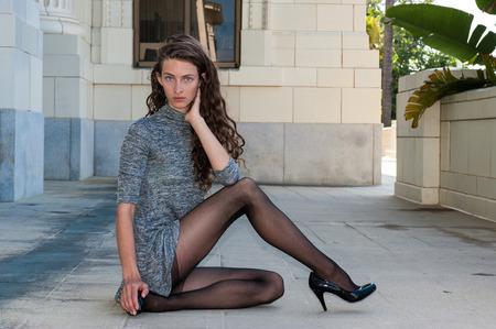 Mooie brunette in zwarte broekiekouse, korte jurk, en pompen met glimp van tops met been gekruist naar rechts.