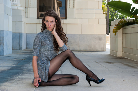 Pretty brunette in black pantyhose, short dress, and pumps with glimpse of tops with leg crossed over facing right.