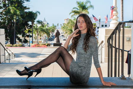 Pretty backlit brunette in black pantyhose, short dress, and pumps seated over Downtown looking forward.