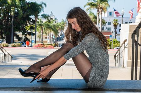 Mooie brunette met achtergrondverlichting in zwarte panty, korte jurk en pumps zitten over Downtown om haar schoen aan te passen.