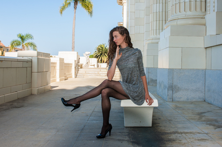 Pretty brunette in black pantyhose, short dress, and pumps seated on bench with leg crossed over and looking distant.
