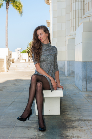 Pretty brunette in black pantyhose, short dress, and pumps seated on bench with leg crossed over and looking ahead.