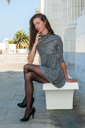 Pretty brunette in black pantyhose, short dress, and pumps seated on bench with leg crossed over and looking forward. 版權商用圖片