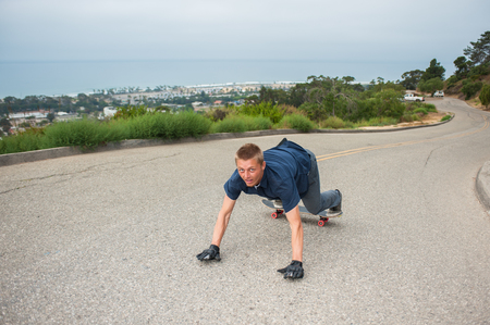 내리막 스케이트 보더는 낀 손을 사용하여 오르막보기에서 모퉁이 만 돌면 볼 수 있습니다. 스톡 콘텐츠