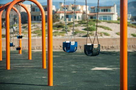 Empty playground swings swaying in the ocean breeze at the neighborhood beach in the morning.