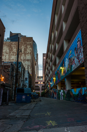 Downtown Phoenix side alley with colorful artwork reflecting the morning light on August 11, 2017.  Trash dumpsters line the opposite side. Editorial