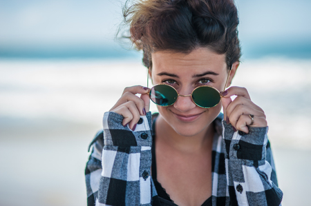 Happy teen head shot at beach with female looking over sunglasses with sassy look. Stock Photo