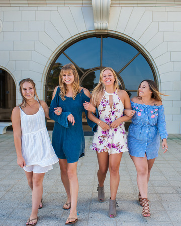 Pretty college girls together in a group walking in white brick courtyard with arms linked. Stock Photo