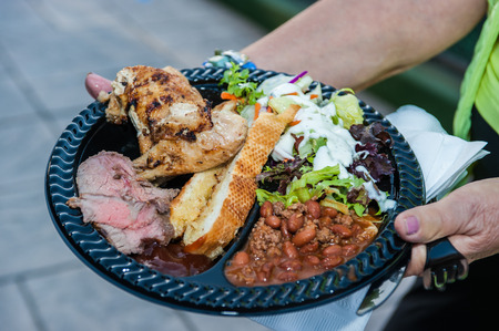 Hospitality accommodations feature a full plate of steak, chicken, salad, bread, and beans. Reklamní fotografie