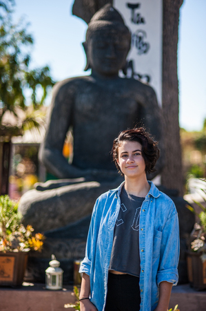 Japanese American teenager girl posed in garden with Buddhist statue in background.