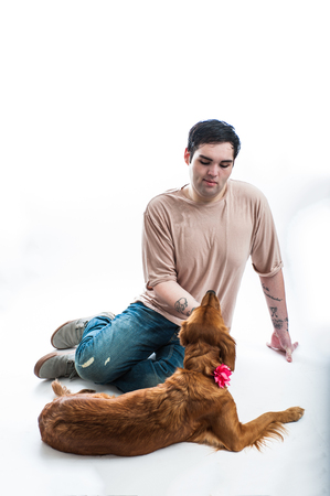 Fair skinned young man amused by his Golden Retriever dog lying on the floor.
