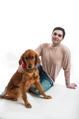 Fair skinned man sharing a moment with his Golden Retriever on the floor.