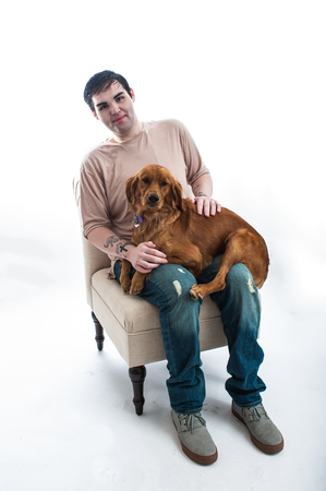 Fair skinned young man seated on chair smiling with his Golden Retriever puppy dog on lap. Stock Photo - 90378629