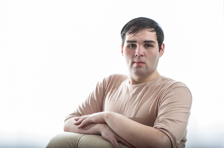 Fair skinned young man leaning in with arms folded across body.