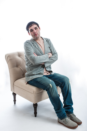 Fair skinned young man seated on chair looking anxious with arms crossed.