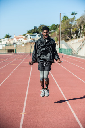 Lean Jamaican athlete jumping rope with intense look on face on track at stadium. Stock Photo