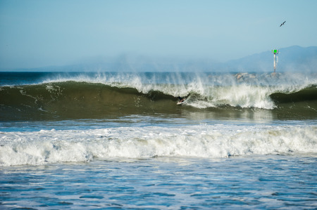 Only disembodied feet of California surfer show as offshore winds create large and hollow tube waves covering his surfboard. Stock Photo