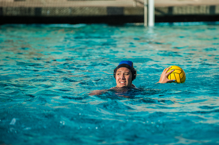 Water polo female athlete showing intense expression as she searches for a teammate to pass the ball.