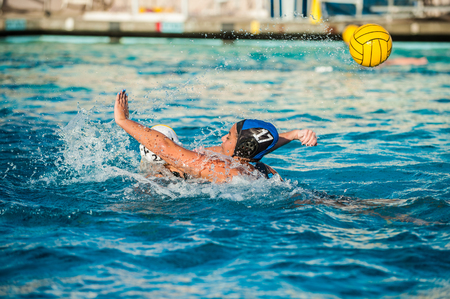 Female water polo player on defense has hand up to block shot as pool water splashes. Stock Photo