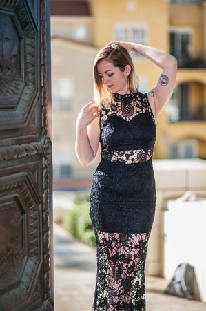 Elegant young female model in formal black lace gown backlit at open door.